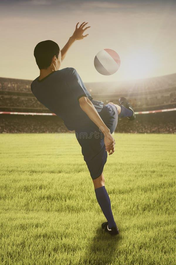 Fotbollspelare som spelar en boll på fältet fotografering för bildbyråer