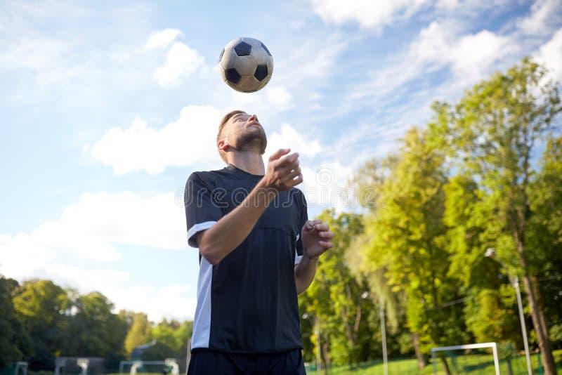 Fotbollspelare som spelar med bollen på fält fotografering för bildbyråer