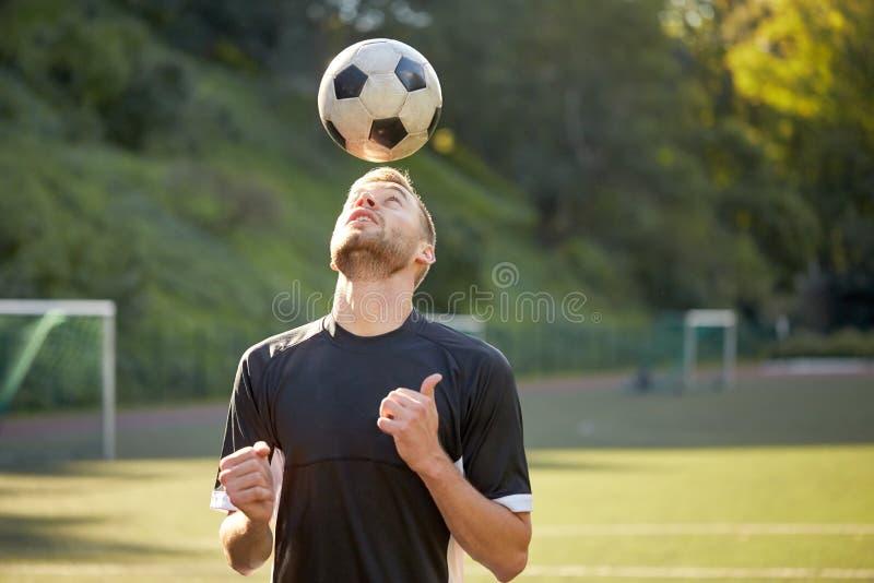 Fotbollspelare som spelar med bollen på fält royaltyfri foto