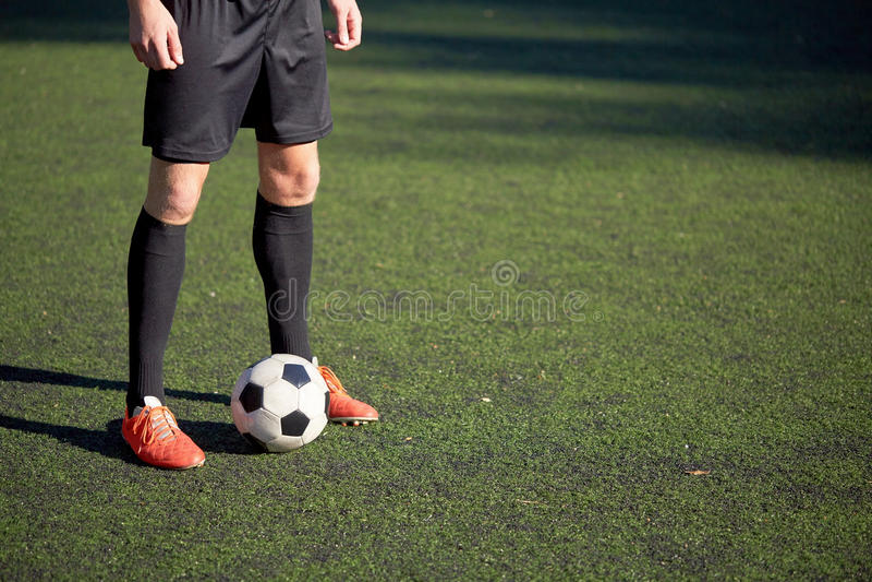 Fotbollspelare som spelar med bollen på fotbollfält arkivfoto
