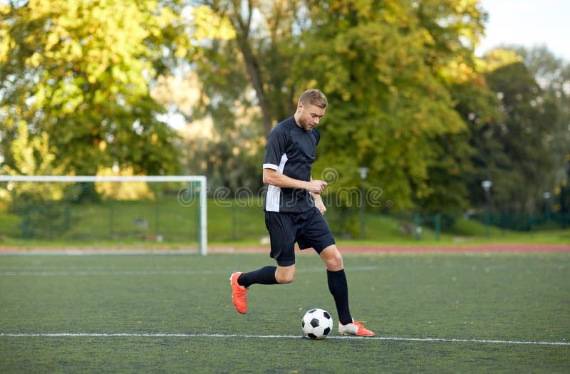Fotbollspelare som spelar med bollen på fotbollfält royaltyfri bild