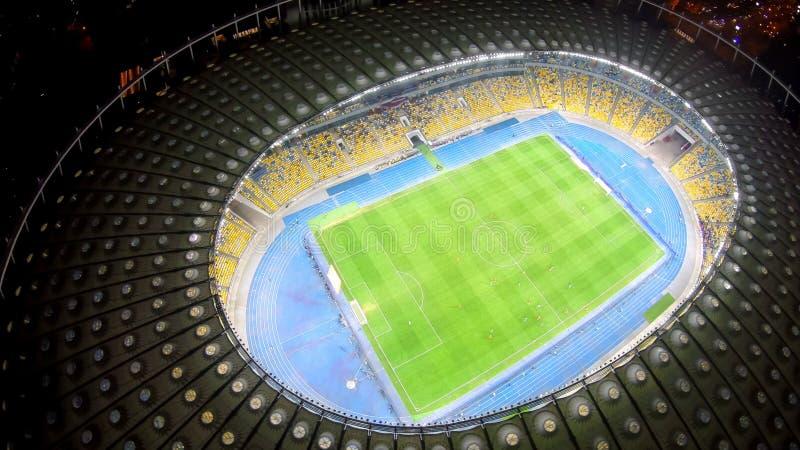 Fotbollspelare som utbildar på stor grön stadion, fantastisk cityscape, aftonmatch fotografering för bildbyråer
