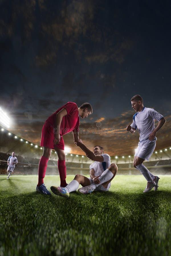 Fotbollspelaren hjälper onother en på panorama för solnedgångstadionbakgrund royaltyfri bild
