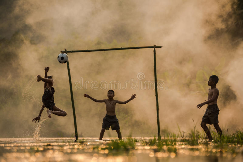 Fotbollsspelare de tre barnen spelar fotboll på royaltyfria foton