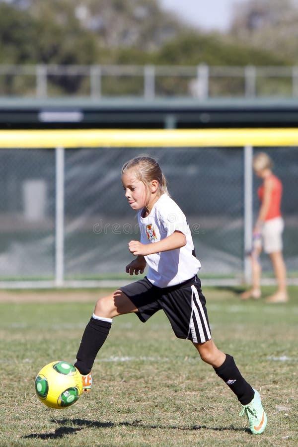 Fotbollsspelare för flickaungdomfotboll som sparkar bollen royaltyfria bilder