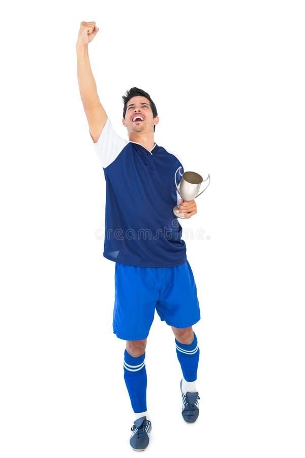 Fotbollsspelare i blå hållande vinnarekopp royaltyfria bilder