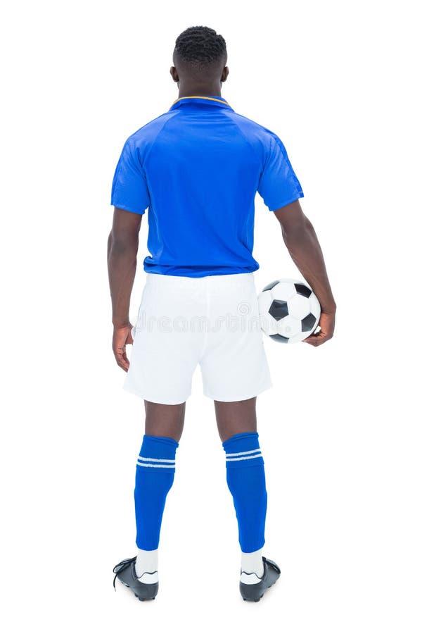 Fotbollsspelare i blått anseende med bollen fotografering för bildbyråer