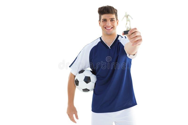 Fotbollsspelare i hållande vinnaretrofé för blå ärmlös tröja arkivbild