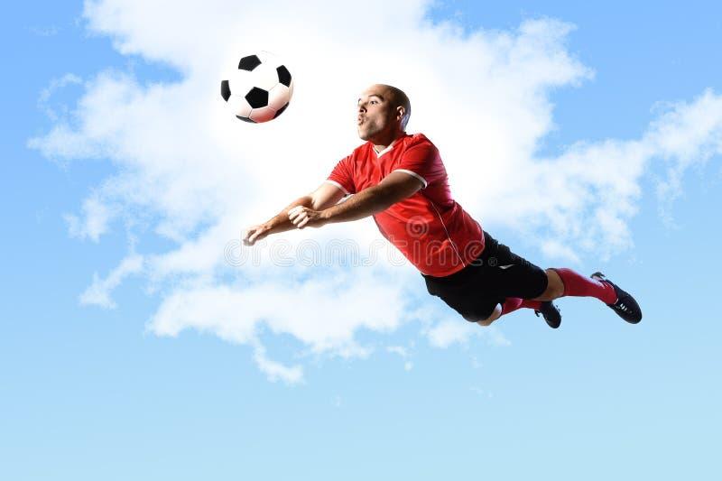 Fotbollsspelare i handlingbanhoppningen för den head sparken som isoleras på blå himmel royaltyfria bilder