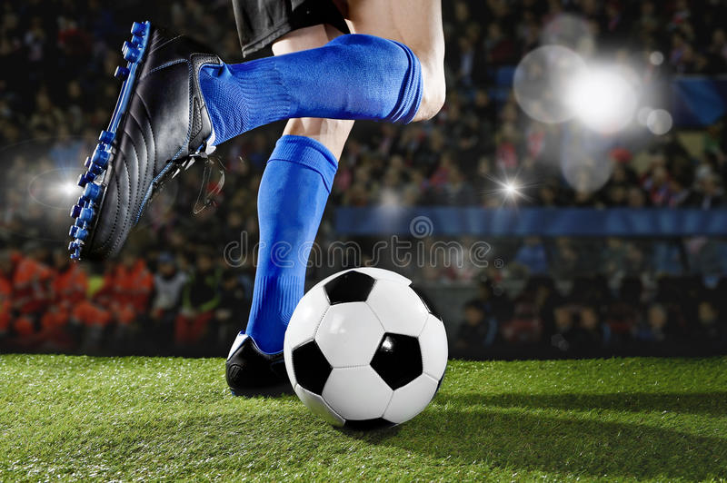 Fotbollsspelare i handlingspring och dregla på fotbollstadion som spelar matchen arkivbild