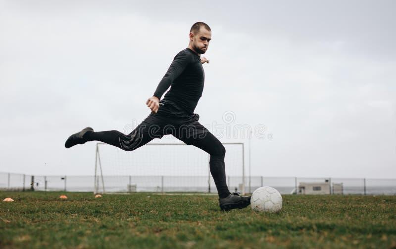 Fotbollsspelare som öva hans sparkar på fältet på en molnig dag Man som spelar fotboll på fält omkring för att sparka bollen royaltyfria foton
