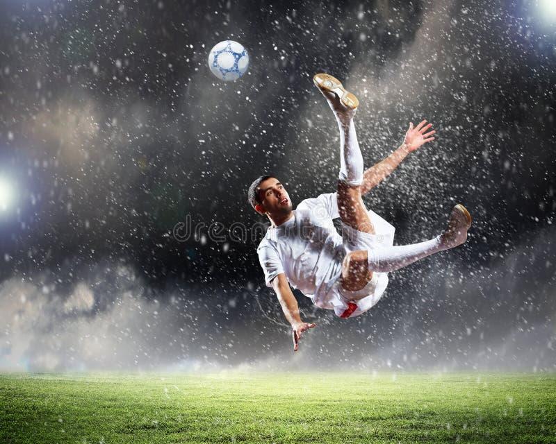 Fotbollsspelareen klockas slag klumpa ihop sig royaltyfria foton