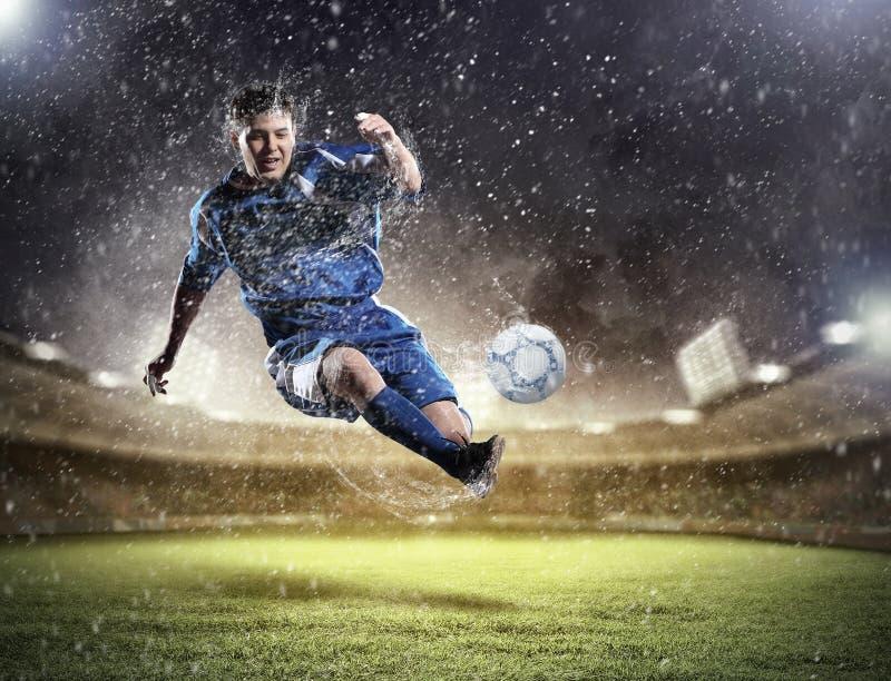 Fotbollsspelareen klockas slag klumpa ihop sig royaltyfria bilder
