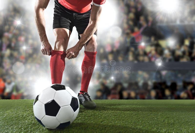 Fotbollsspelaren med bollen som bär svarta skor som justerar hans röda sockaanseende på stadion, kastar arkivfoto
