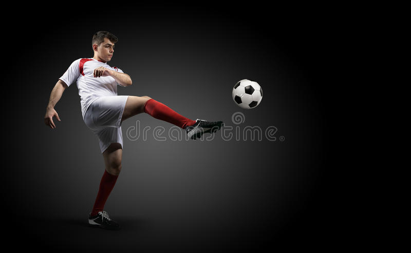 Fotbollsspelaren sparkar en boll på den svarta bakgrunden royaltyfri fotografi