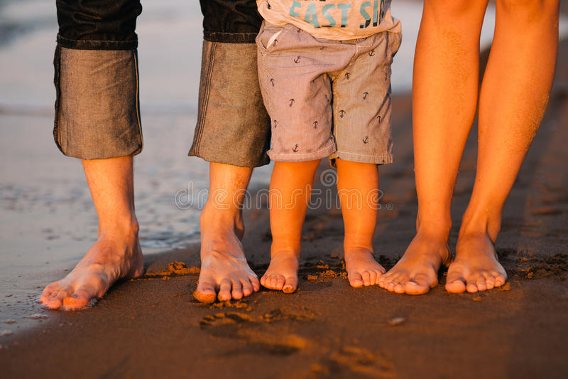 Foten av en ung familj på ett hav sätter på land royaltyfri fotografi