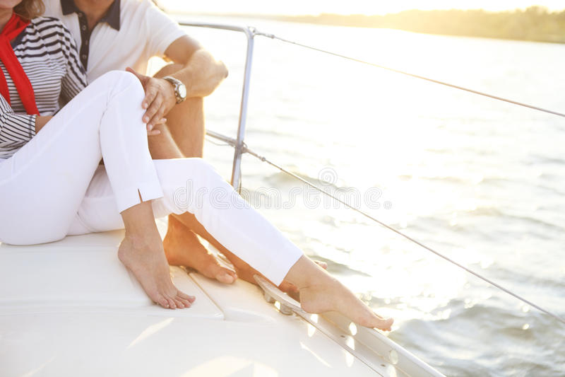 Foten av ett par som stting på segelbåten, pryder i havet arkivfoton