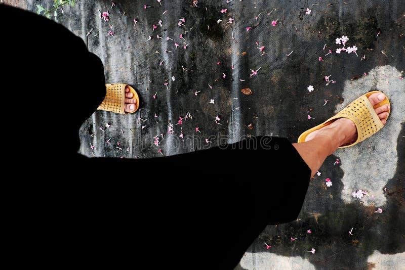 Foten bär svarta flåsanden, plast- sandaler fotografering för bildbyråer