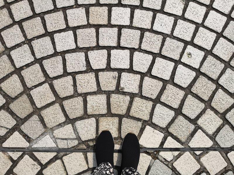 Foten för en person ware svarta skor som står på den gråa kullerstenkurvmodellen som stenlägger på en gata arkivbilder