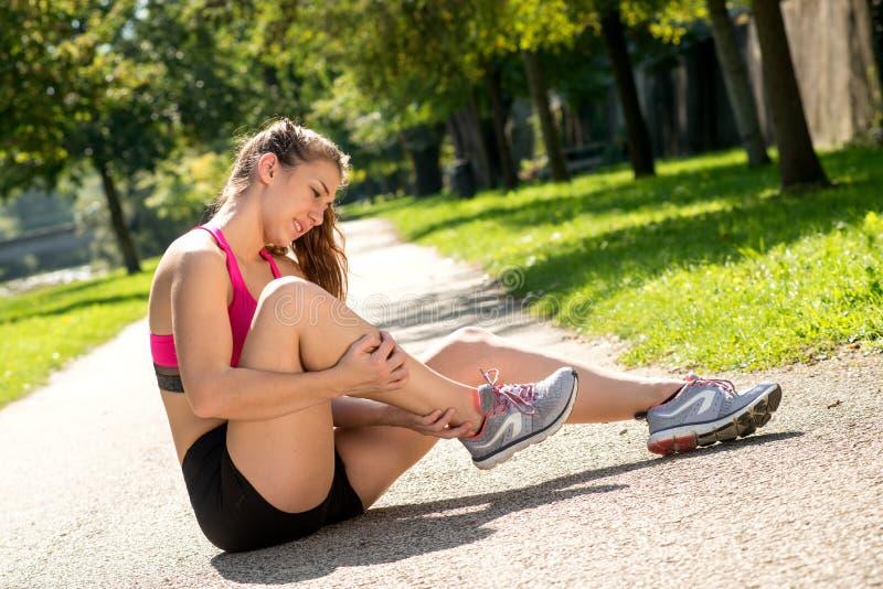 Foten för löparen för den unga kvinnan smärtar den rörande in utomhus royaltyfria bilder