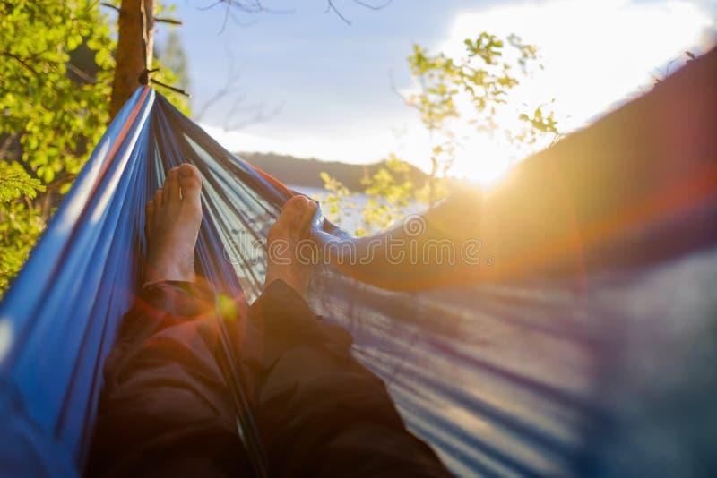 Foten för man` s är den sedda närbilden från en hängmatta i en sommarskog, på en suddig bakgrund av sörjer och en sjö fotografering för bildbyråer