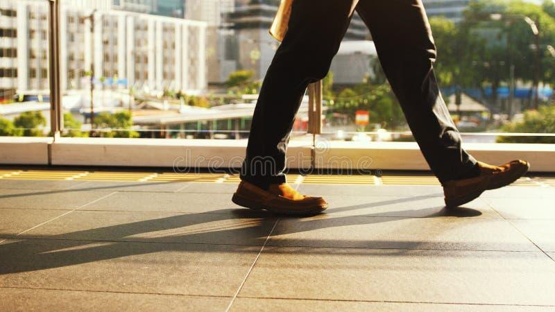 Foten för man` s går på övergångsställe på en upptagen dag i mitten av staden på en solig dag på vägen på arkivbilder