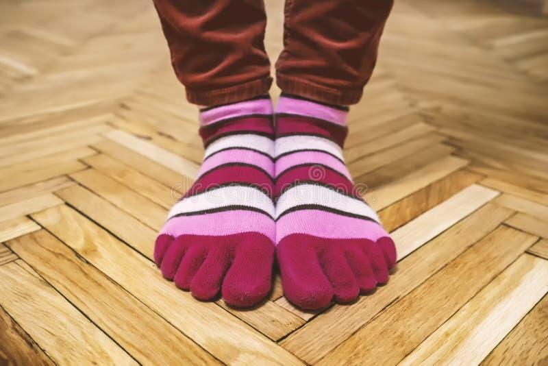 Foten, i att roa mång--färgade randiga sockor, står på en gammal parkett royaltyfri foto