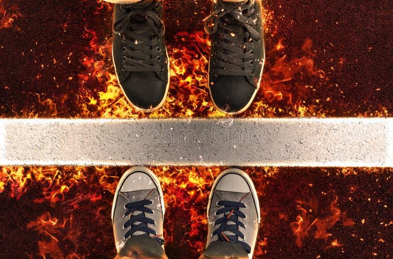 Foten i gymnastikskor som står bredvid den vita gatan, fodrar i flamma royaltyfri illustrationer