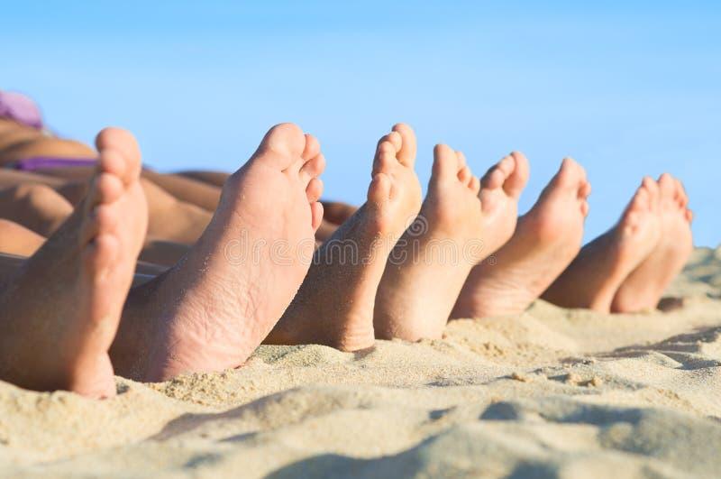 Foten kopplar av på stranden royaltyfria bilder