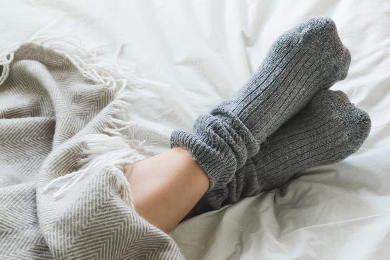 Foten korsade med gråa sockor på säng under filten fotografering för bildbyråer