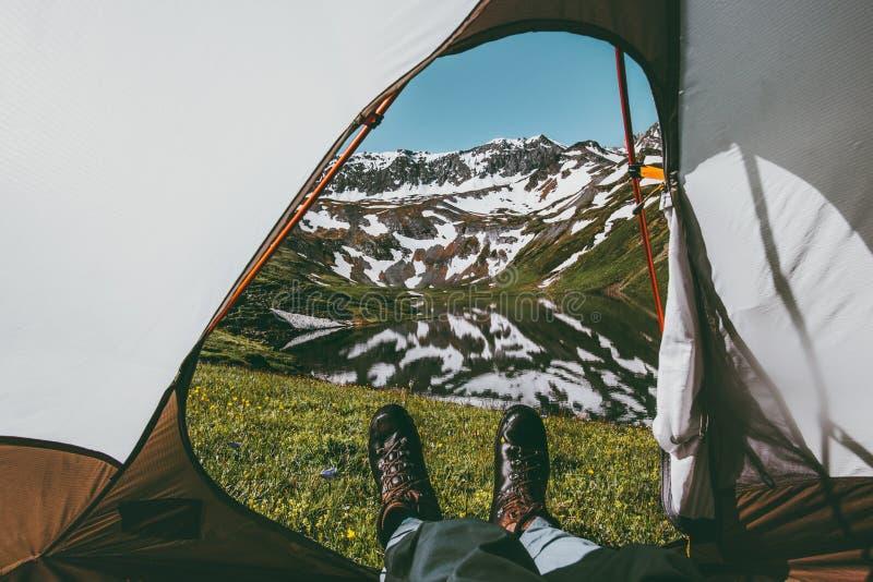 Foten Man att koppla av tycka om berg och sjösikt från den campa ingången för tältet arkivbilder