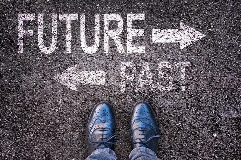 Foten och ord framtid och forntid målade på en väg arkivfoto