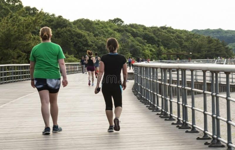 Fotgängare och joggers på en strandpromenad vid stranden fotografering för bildbyråer