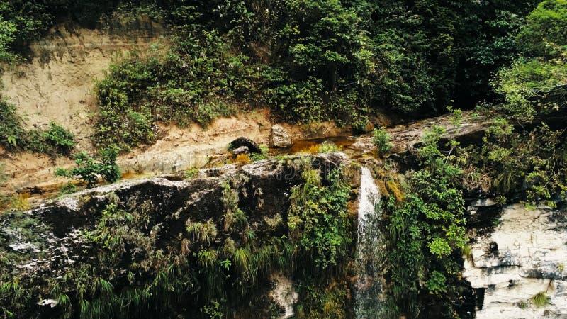 Foto aérea cinemático do zangão da cachoeira e uma associação pequena profundamente na selva da floresta úmida no parque nacional fotos de stock royalty free