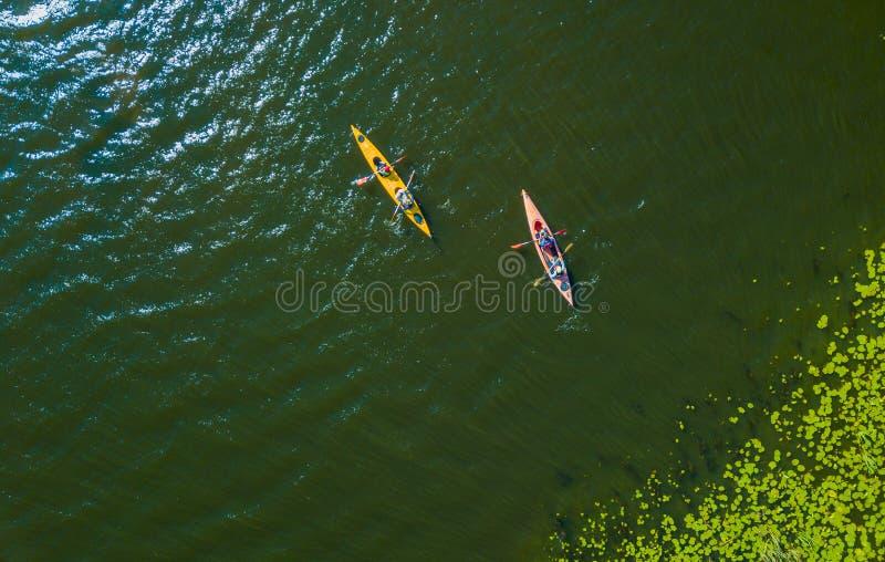 Foto aérea da opinião de olho de pássaro do zangão da família feliz com as duas crianças que apreciam o passeio do caiaque no rio imagens de stock royalty free