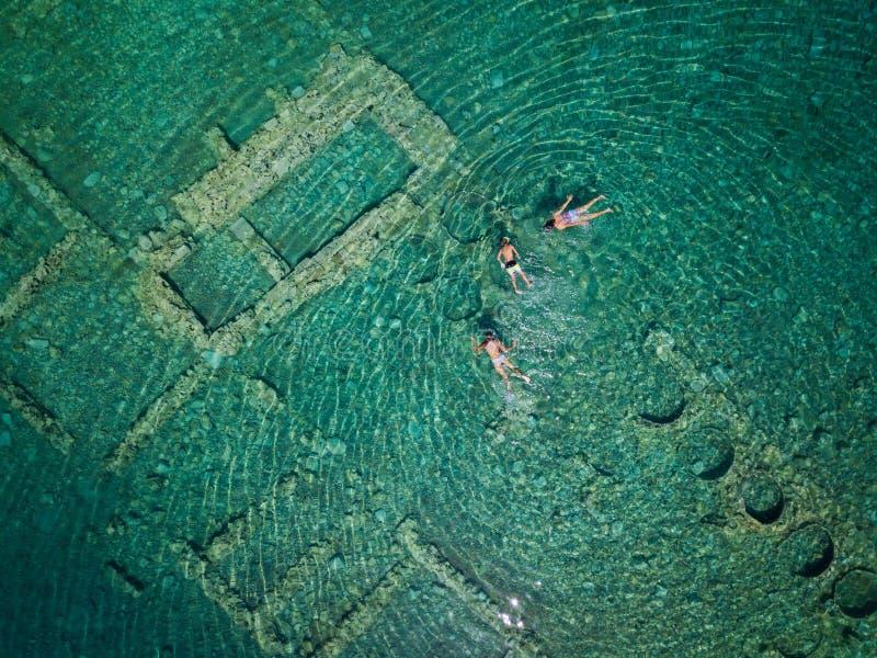 Foto aérea da opinião do olho do ` s do pássaro do zangão dos turistas que mergulham acima da cidade afundado velha de Epidauros, imagem de stock royalty free