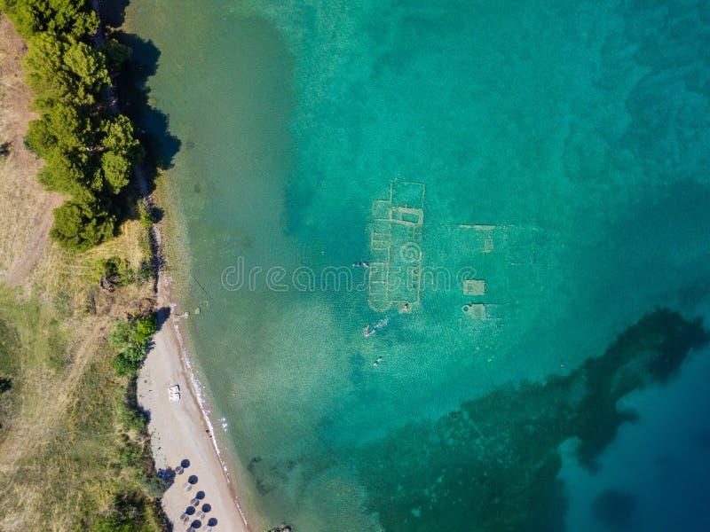 Foto aérea da opinião do olho do ` s do pássaro do zangão dos turistas que mergulham acima da cidade afundado velha de Epidauros, fotos de stock royalty free
