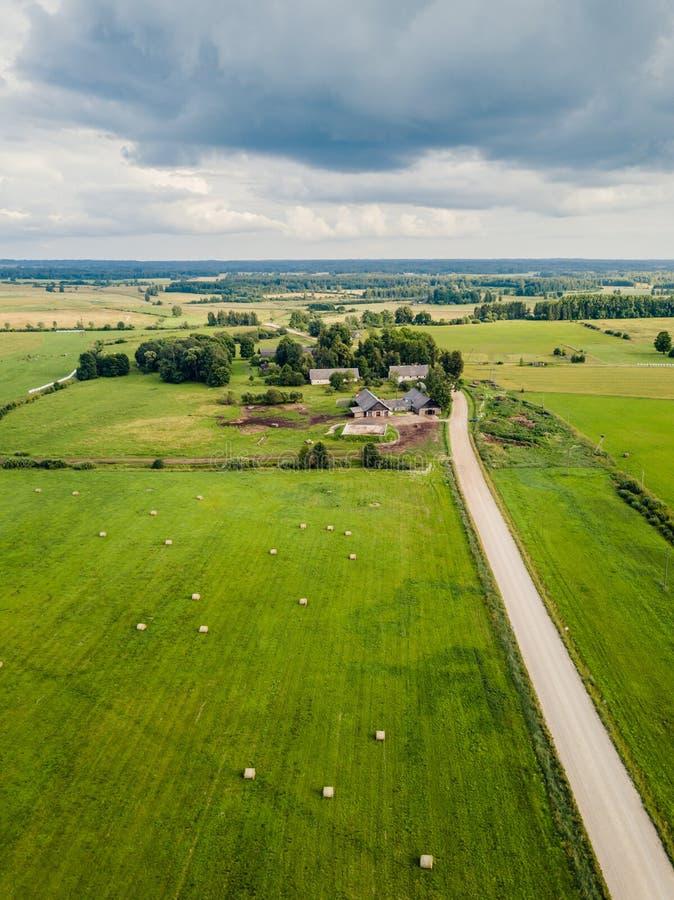 Foto aérea de casas velhas do fazendeiro com a estrada por seus campos do lado e da agricultura em torno dela na mola adiantada e imagens de stock