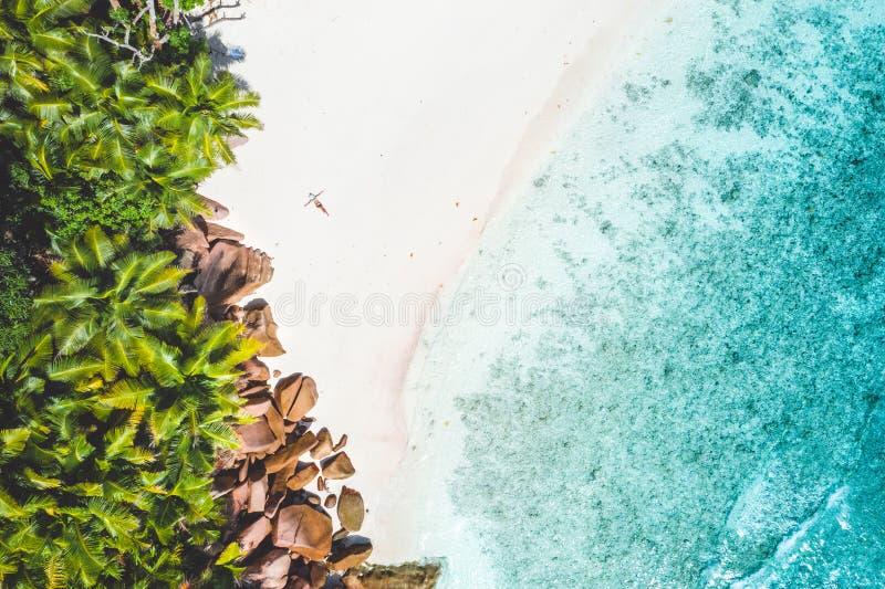 Foto aérea de la playa blanca tropical exótica de la arena con la mujer joven que toma el sol la relajación Concepto de vacacione foto de archivo libre de regalías
