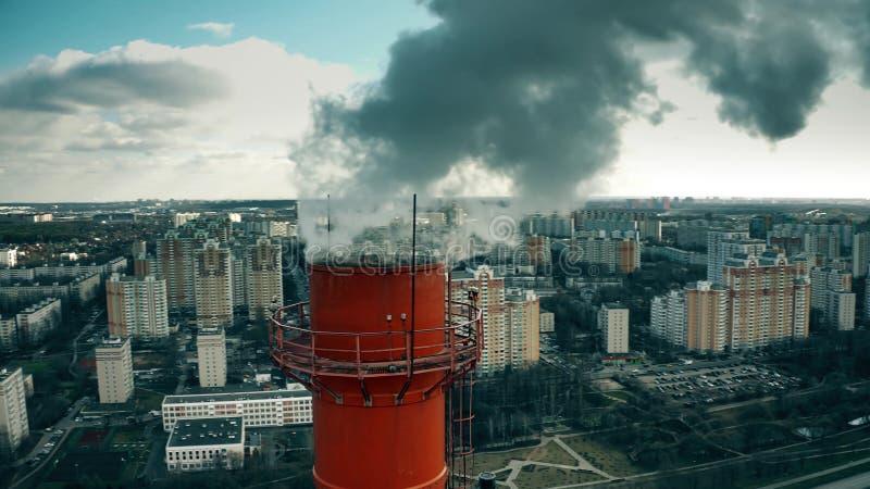 Foto aérea de uma pilha de fumo industrial elevada sobre o fundo da área residencial da cidade fotos de stock royalty free
