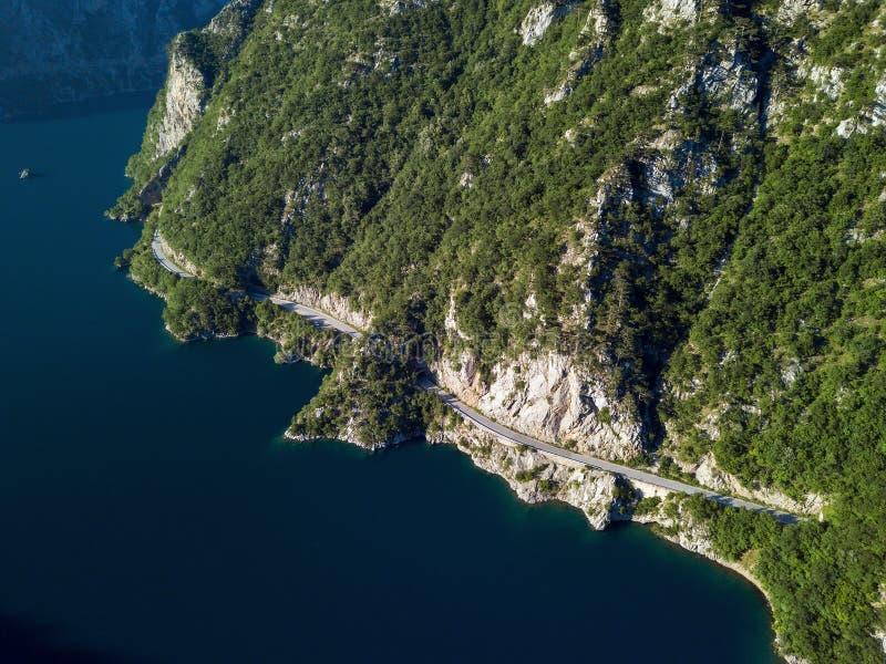 Foto aérea de un largo camino sinuoso en el lago Piva en Montenegro fotos de archivo libres de regalías