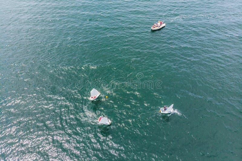 Foto aérea del abejón de adolescentes jovenes en los pequeños barcos de navegación que compiten en la regata en el mar esmeralda  imágenes de archivo libres de regalías