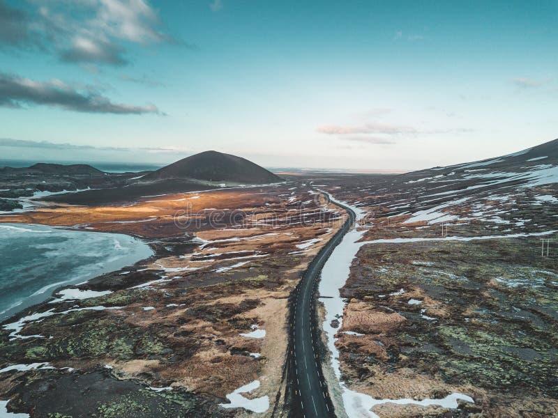Foto aérea del abejón de una carretera vacía 1 del lago y de la calle con una montaña volcánica enorme Snaefellsjokull en la dist imagen de archivo