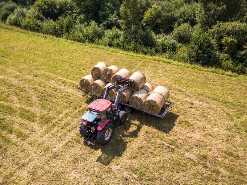 Foto aérea del abejón del granjero Harvesting Hay Rolls en el trigo F foto de archivo libre de regalías