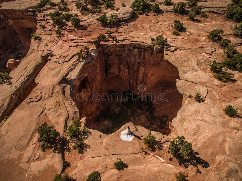 Foto aérea del abejón - mujer en un vestido de boda que pasa por alto una dolina en el desierto de Utah fotos de archivo libres de regalías