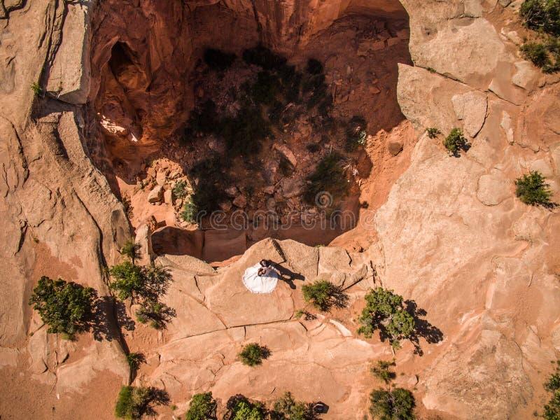 Foto aérea del abejón - novia y novio que pasan por alto una dolina en el desierto de Utah foto de archivo libre de regalías
