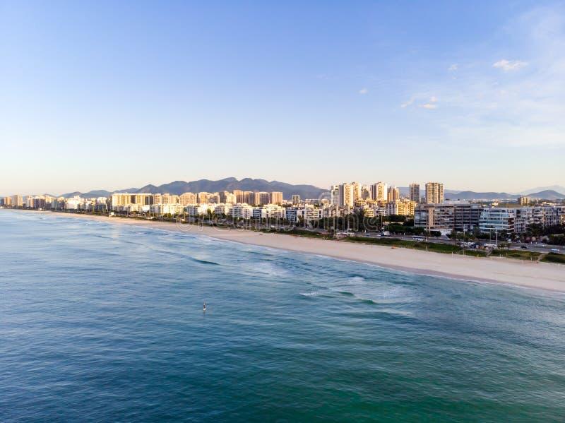 Foto aérea del paisaje de la playa de Barra da Tijuca, con las ondas estrellándose en la playa durante salida del sol, con el fre foto de archivo libre de regalías