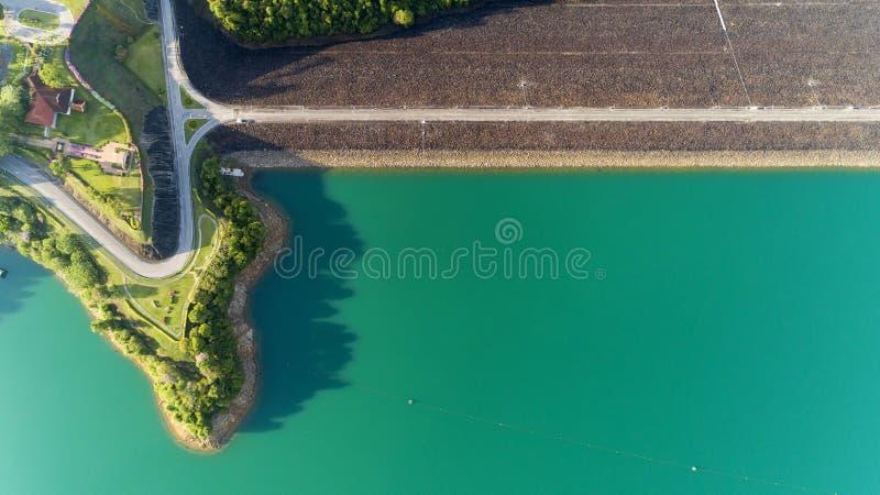 Foto aérea do zangão de voo da estrada asfaltada em torno da represa, paisagem bonita da natureza fotografia de stock royalty free