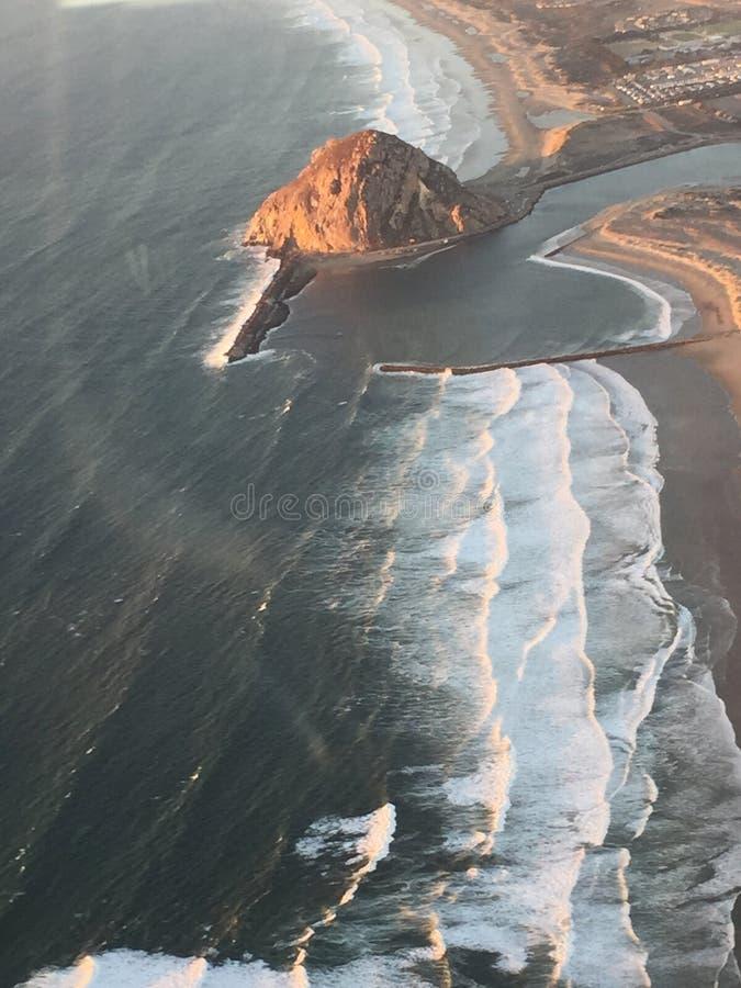 Foto aérea en la puesta del sol - roca iluminada de la bahía de Morro por puesta del sol imagen de archivo