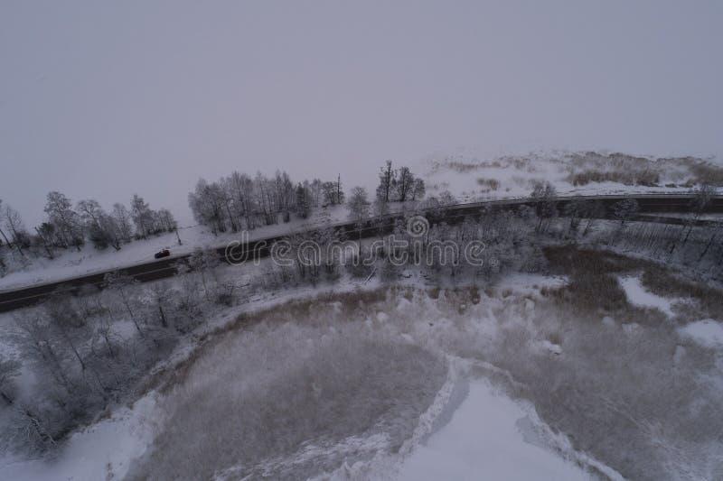 Foto aérea hermosa del lago congelado del hielo y camino en Suecia, Escandinavia imagen de archivo